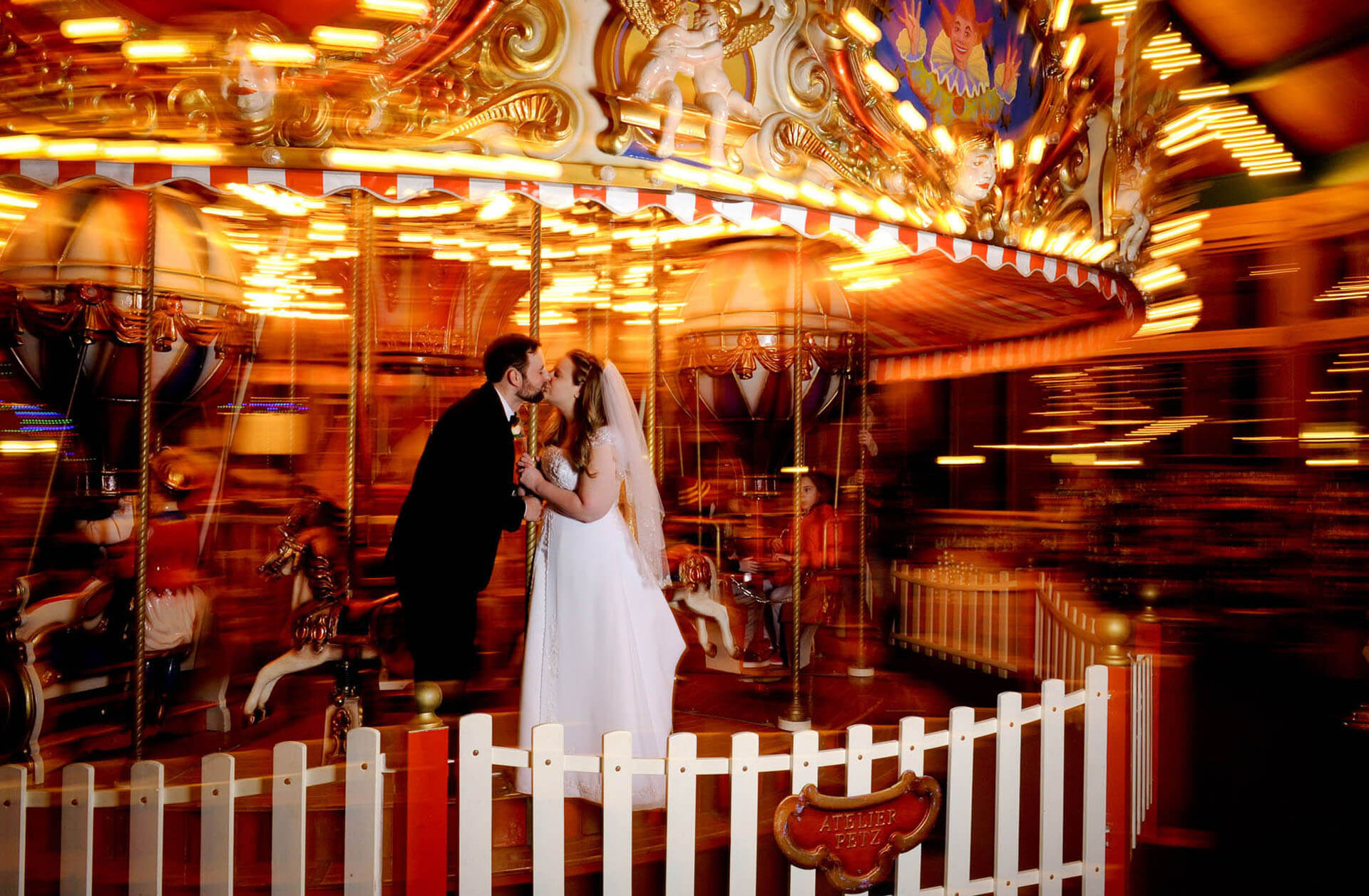The bride and groom ride the carousel at their Canterbury Village wedding in Lake Orion, Michigan during their Michigan winter wedding.