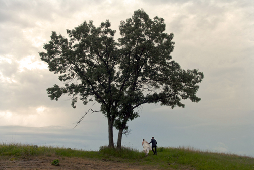 =Michigan bride and groom climb a hill at the Indian Springs Metro Park after their Michigan wedding.