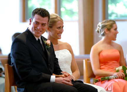 Fun Michigan wedding photographer takes photos during the ceremony at a catholic service in Auburn Hills, MI
