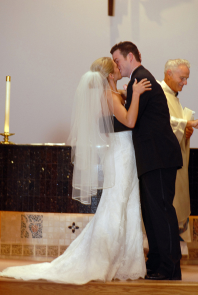Troy wedding photojographs of a couple's nuptual kiss at the altar of their Auburn Hills catholic church