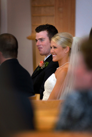 Michigan wedding photojournalist captures small moments like a couple's reaction during communion at the Troy, Michigan Catholic church