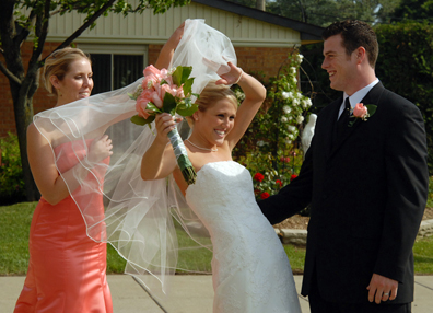 Troy wedding photographers capture fun moments like the group effort it took to get Kristin's veil from blowing away