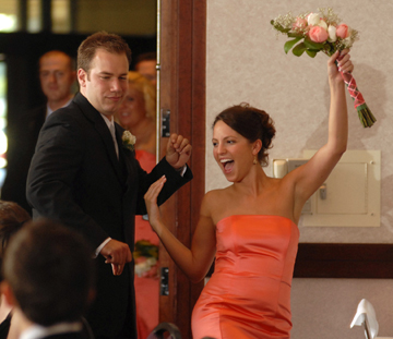 A groomsman and bridesmaid make their grand entrance into the ballroom at the best western Sterlin Inn in Michigan