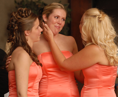 wedding photojournalists capture great wedding moments like these sisters having a moment while their sister dances with their father