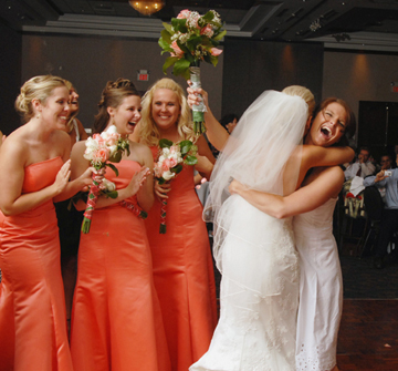 Bride congratulates the bouquet grabber after the toss at their wedding recpetion in Troy Michigan