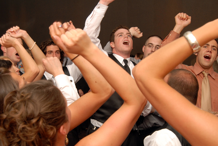 Groom sings hail to the victors at his wedding reception in Troy Michigan as photographer takes pictures unnoticed