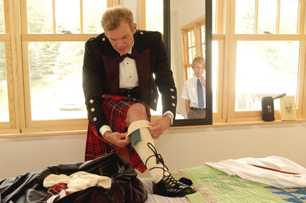 The ring bearer watches in the mirror as his father puts on his final Scottish kilt preparations as he gets ready for his backyard Ann Arbor wedding.