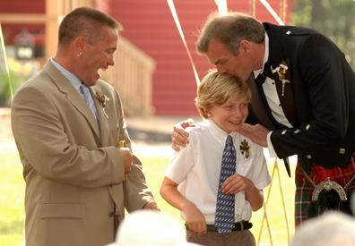 The Scottish groom kisses his son during their Ann Arbor backyard wedding.