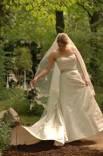 The Scottish bride adjusts and fiddles with her long veil after her back yard wedding ceremony.