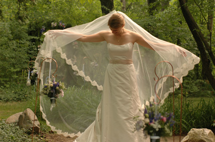 The Scottish bride adjusts her lenghly veil after her Ann Arbor backyard wedding ceremony. This garden provided wonderful backyard wedding photography.