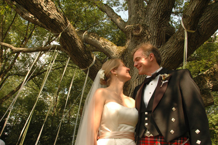 The Scottish bride and groom pose under the gigantic oak tree they were married under after their Ann Arbor back yard wedding.
