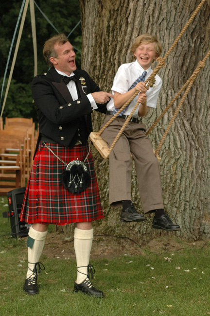 The Scottish groom gives his son a push on the swing shortly after their backyard wedding ceremony in ann arbor, michigan