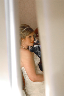 The bride peeks from behind a curtain separating her from the groom at her Troy MI wedding