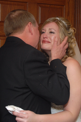 The bride cries as her father kisses her after her wedding ceremony in Troy, Mi