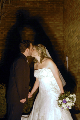 The bride and groom kiss outside under funky lights at their Troy, Michigan reception Hall