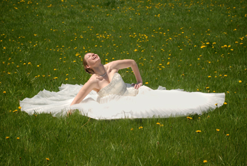 The bride plays in a field of dandelions at her Michigan farm.