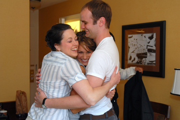 The groom gets hugs from his sister and sister in law before his Dearborn Inn wedding.