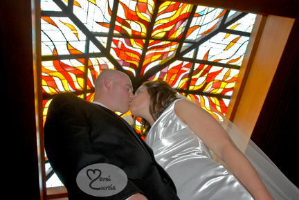 The bride and groom kiss under the stain glass at their Catholic church in Macomb Michigan