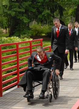 The best man goofs around in a wheelchair after the wedding ceremony.