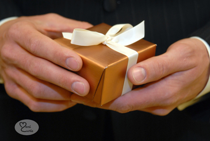 Groom holds a box with a gift for his bride