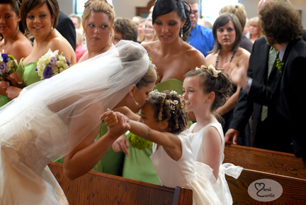 The bride kisses the flowergirl during the ceremony