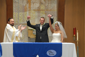 The bride and groom raise their arms during the wedding ceremony in chelsea, Michigan