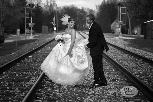 The groom helps the bride across the railway tracks in Chelsea Michigan