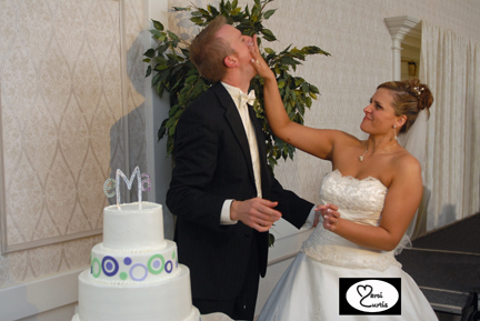 The bride slams wedding cake into the groom's face during their Ann Arbor wedding reception.