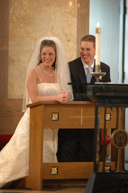 The bride and groom watch their guests during their Michigan catholic wedding.