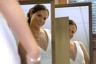 MSU bride checks herself out in two mirrors before her Lansing wedding in Michigan.