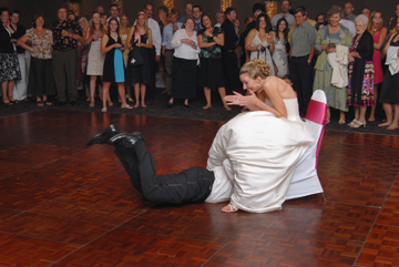 Groom dives under brides dress to retrieve the garter at a Macomb County Michigan wedding