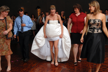 Bride teaches a new dance to wedding guests by hiking up her dress so they can follow along during Macomb County wedding.