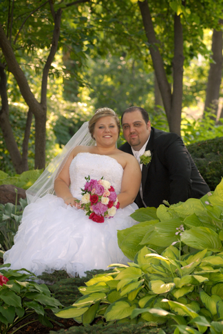 Wedding couple pose for photos at a park in Macomb, MI