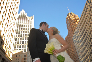 The bride and groom kiss downtown Detroit, MI