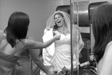Warren MI bride laughs as she gets bustled in the bathroom.