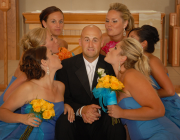 Groom's not too sure he wants to be kissed by beautiful bridesmaids at a wedding shot by michigan wedding photographer