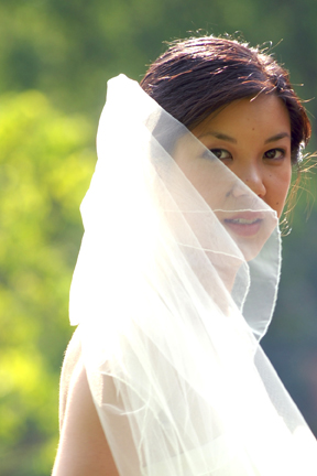 The bride tries to fight with her veil during photos at the Cobblestone Farm in Ann Arbor Michigan