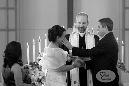 Groom wipes a tear from his bride's cheek during ceremony
