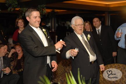 The groom plays Wii with his grandfather during the wedding reception