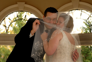 The groom plays peek a boo with the bride's veil in michigan