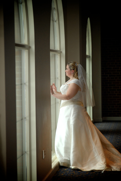 St. Johns bride against some of their windows before her wedding