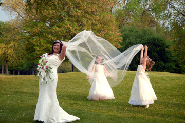 Bride gets her veil fluffed by bridesmaid during Black River Country Club MI wedding