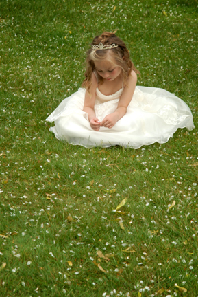 Flower girl picks at weeds after a Port Huron Michigan wedding
