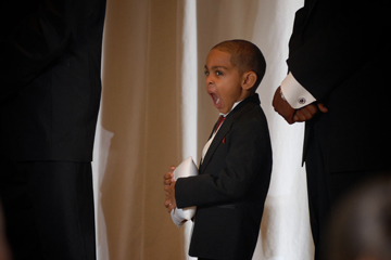 The ring bearer lets loose a yawn during the wedding ceremony in Redford, MI