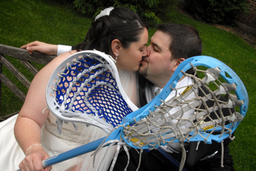 =bride and groom kiss under the cross of lacrosse sticks at their Henry Ford Museum wedding in Dearborn, Mi