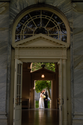 The Bride and kiss in the archway of their Henry Ford Museum wedding in Dearborn, MI