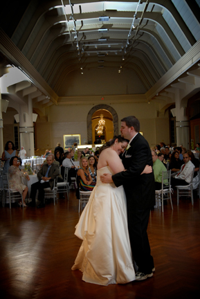 bride and groom dance in the Henry Ford Museum at their reception in Dearborn, Michigan