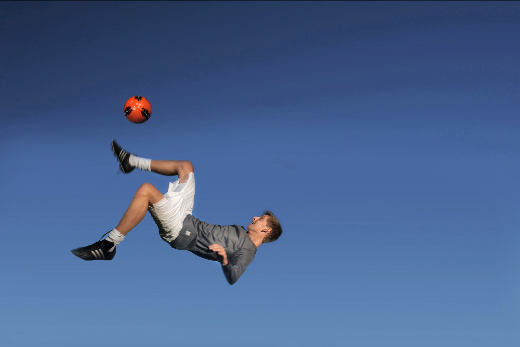 A Birmingham senior in Michigan leaps into the air showcasing his soccer skills for his senior photos.
