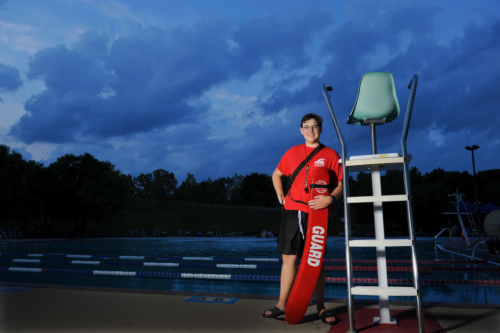 Lifeguard and Troy High senior poses at his Troy pool at dusk for this dramatic and creative senior photo near Troy, Michigan.