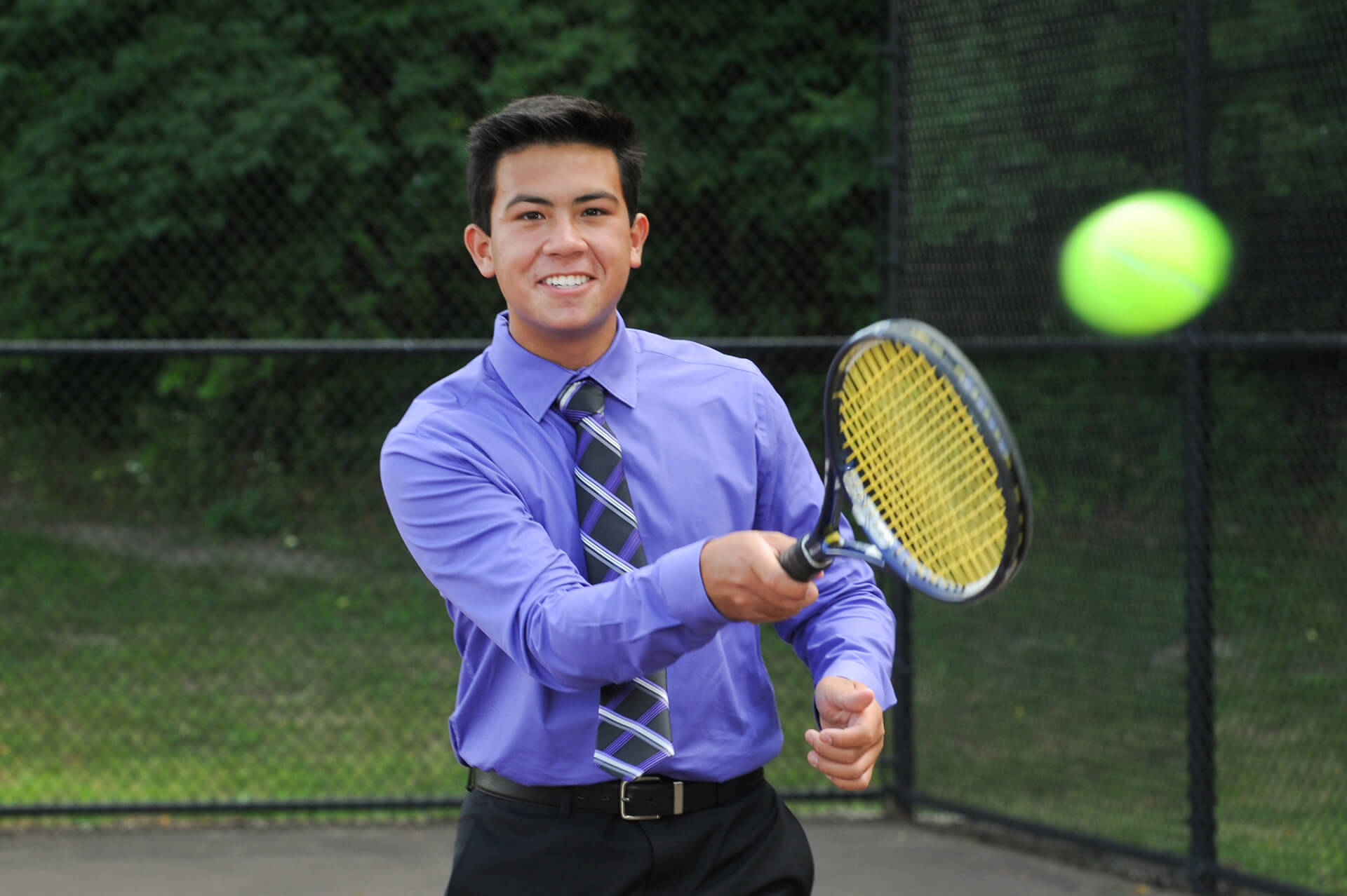 Troy Athens high school senior poses in his suit while playing tennis near Rochester, Michigan.